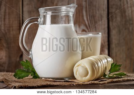 Natural rustic whole milk in a glass jug and a glass suluguni cheese and parsley leaves on the old wooden background closeup