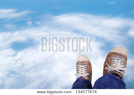 Two legs of the men wore blue jeans statements and brown leather shoes with clouds sky background.
