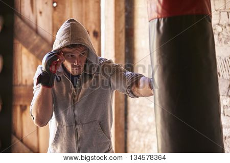 Young Male Boxer Working Out With Punchbag In Gym