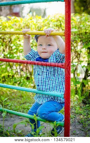 Little toddler climbing the ladder having fun at playground in summer. Cute young boy kid or child playing outdoors on playground. Stylish little baby boy in fashionable bow-tie is clapping hands.