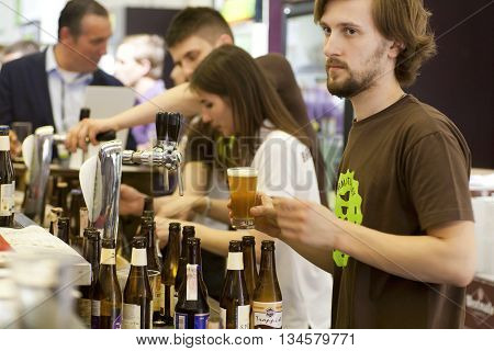 KYIV, UKRAINE - MAY 21, 2016: Bartender pours craft tap beer in busy pub of Beermaster Day Festival on May 21, 2016. Kiev is the 8th most populous city in Europe.