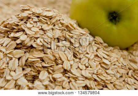 grits are scattered on a surface, rounded shape the processed grains, near a heap of crude grain one green apple lies,