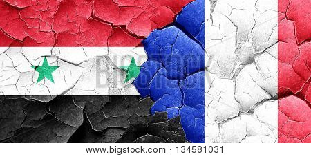 Syria flag with France flag on a grunge cracked wall