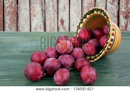 Fresh plums in basket on a wooden table