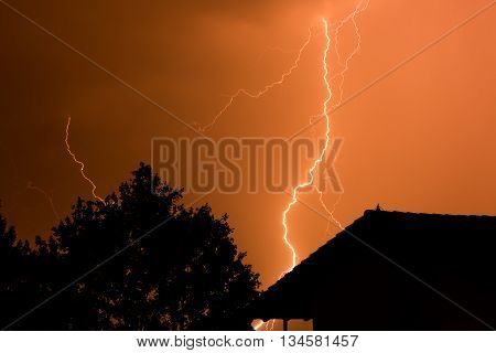 Thunderbolt with tree and house in red sky during strike