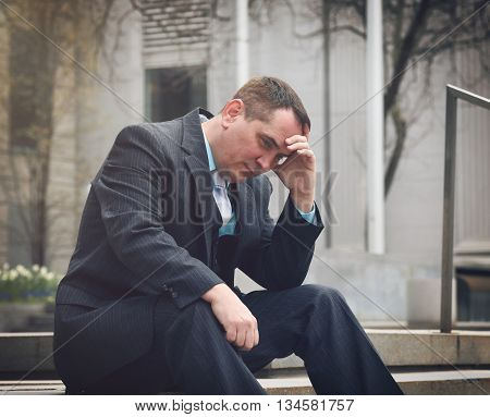 A business man is worried and stressed in a suit outside a city for a financial unemployment or economy concept.