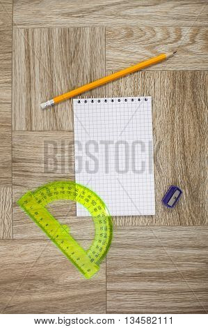 Note Book, Pencil And Protractor Ruler On A Wooden Texture