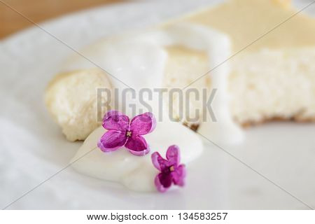 Lemon cheesecake decorated with individual lilac blooms. Intentional shallow depth of field with focus on the lilac flower.