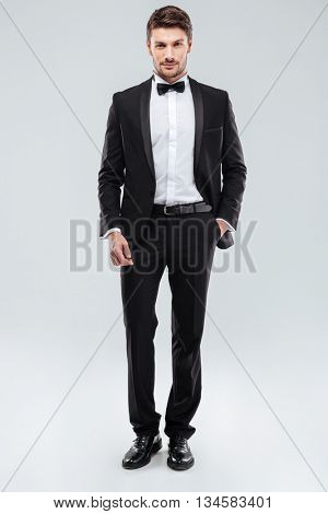 Confident attractive young man in tuxedo standing with hand in pocket