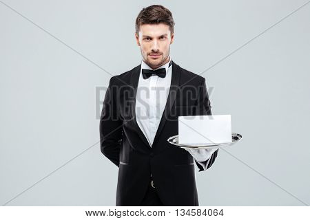 Confident young butler in tuxedo holding blank card on tray