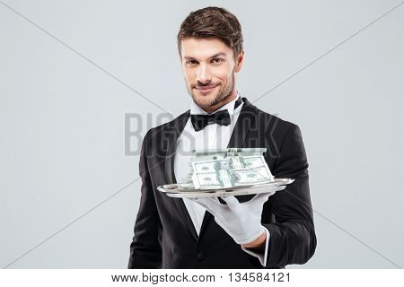 Smiling young waiter in tuxedo and gloves holding tray with money