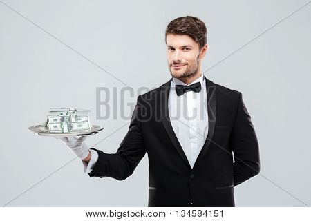 Gorgeous young butler in tuxedo standing and holding tray with money