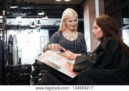 Happy young woman with hairdresser choosing hair color from palette samples at salon
