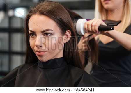 Close-up portrait of a stylist drying woman hair in beauty salon