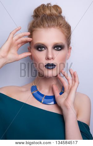 Beauty Fashion Model Woman face, perfect make-up. Sexy dark blue Lips. Beautiful Blond Woman with creative Makeup. Smokey eyes, brown eyes. Beauty Cosmetic Concept Girl Face dark Background
