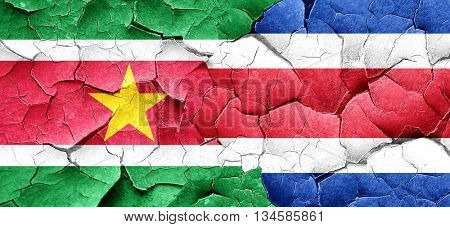 Suriname flag with Costa Rica flag on a grunge cracked wall