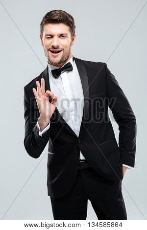 Smiling young man in tuxedo with bowtie winking and showing ok sign
