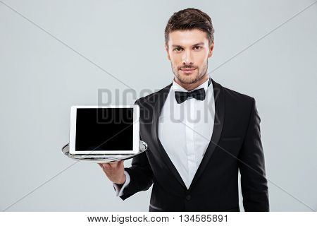 Portrait of attractive young butler in tuxedo with bowtie holding blank screen tablet on tray