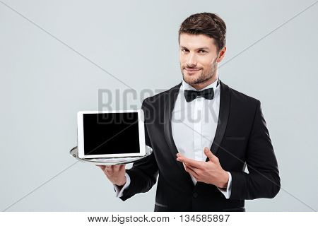 Confident young butler in tuxedo holding and pointing at blank screen tablet on tray
