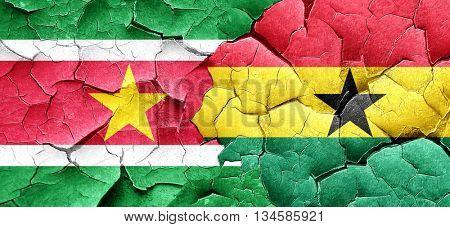 Suriname flag with Ghana flag on a grunge cracked wall