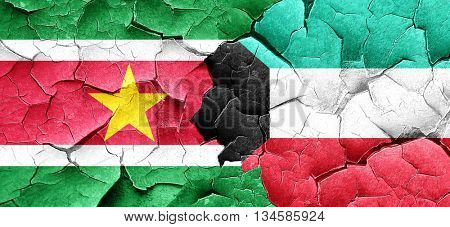 Suriname flag with Kuwait flag on a grunge cracked wall