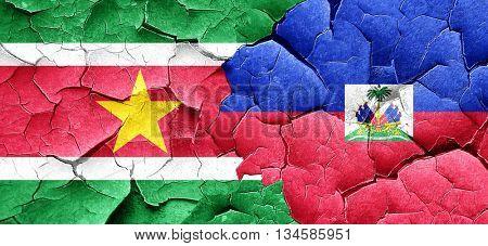 Suriname flag with Haiti flag on a grunge cracked wall