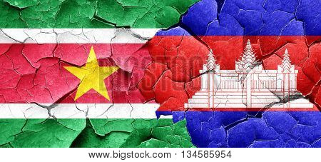 Suriname flag with Cambodia flag on a grunge cracked wall
