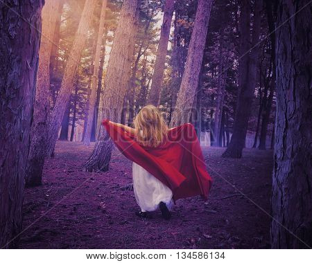 A little girl wearing a white dress and red cape running in the woods with fall leaves for a surreal fairy tale or adventure concept.
