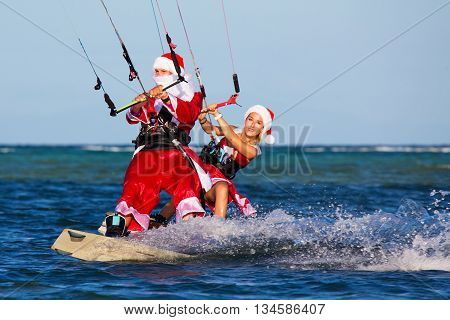 Beautiful young girl and man on the kites in the costume of Santa Claus. Christmas and New year on a tropical island. Extreme Sport Kitesurfing