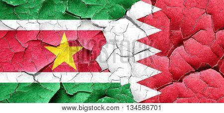 Suriname flag with Bahrain flag on a grunge cracked wall