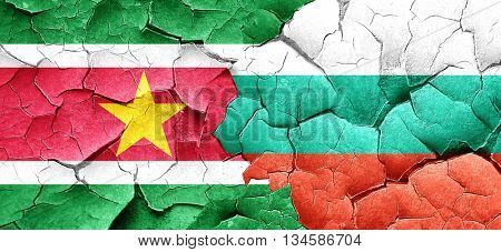 Suriname flag with Bulgaria flag on a grunge cracked wall