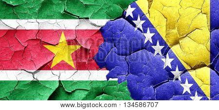 Suriname flag with Bosnia and Herzegovina flag on a grunge crack