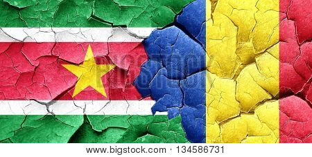 Suriname flag with Romania flag on a grunge cracked wall