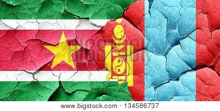 Suriname flag with Mongolia flag on a grunge cracked wall
