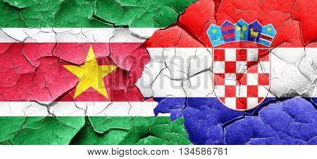 Suriname flag with Croatia flag on a grunge cracked wall