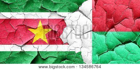 Suriname flag with Madagascar flag on a grunge cracked wall