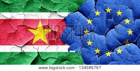 Suriname flag with european union flag on a grunge cracked wall