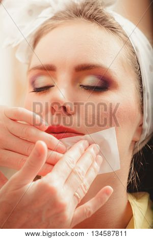 Make up artist using oil absorbing tissues sheets. Closeup of visagiste and pretty young woman girl. Beauty and makeup concept.