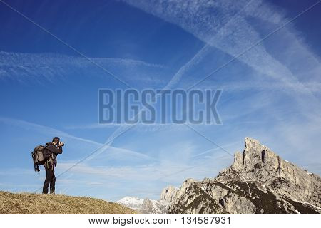 Hiker photographer taking photos on a mountain top in alpine landscape enjoying the view. Active lifestyle natural environment freedom and sports concept. Big blue sky in the background.