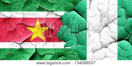 Suriname flag with Nigeria flag on a grunge cracked wall