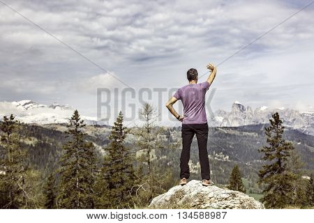 Hiker on a mountain top pasture looking for the right way in alpine landscape being lost. Active lifestyle natural environment orientation and sports concept. Dramatic sky in the background.