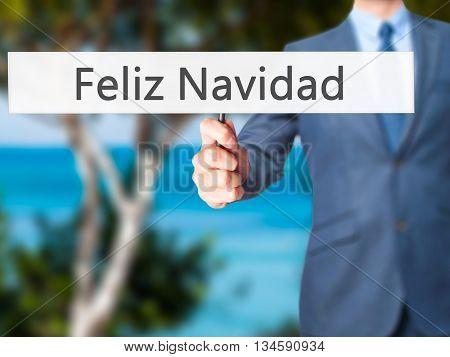 Feliz Navidad (merry Christmas In Spanish) - Businessman Hand Holding Sign
