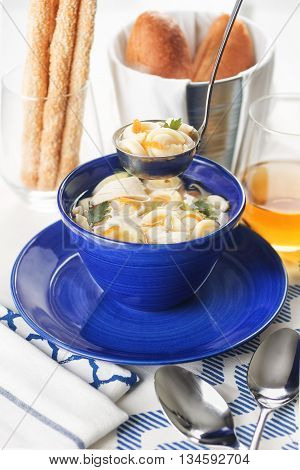 Chicken noodle soup is poured ladle into a blue colored ceramic bowl