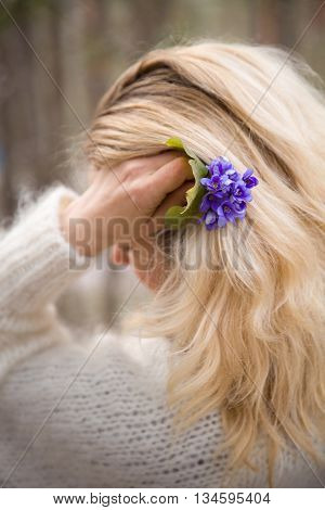 Beautiful flowers in hands of a young blond woman in white cardigan. First spring flowers in a forest. Beginning of spring in a forest.