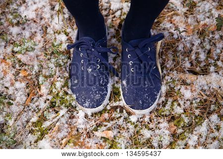 Feet in blue sneakers standing on ground in forest. Outdoors. First snow in the park.