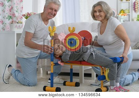 senior parents and granddaughter doing exercise at home