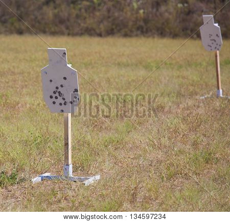 Two steel targets on a field that are used for firearm practice