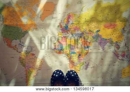 Beautiful Concept For Summer Travel. Small Children's Shoes On The World Map. Planning A Summer Vaca