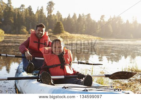 Father and son kayaking on rural lake, close up