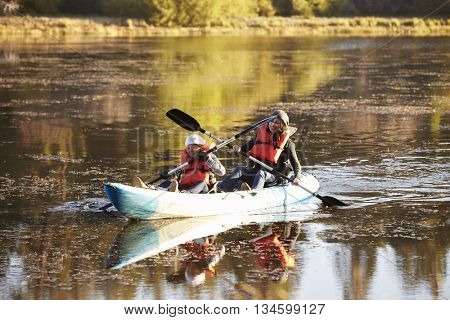 Mother and daughter kayaking together on a lake, close up